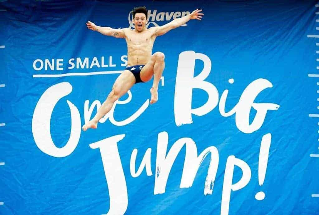 Tom Daley in in front of Craig Taras One Big Jump Banner Printed by Fantasy Prints